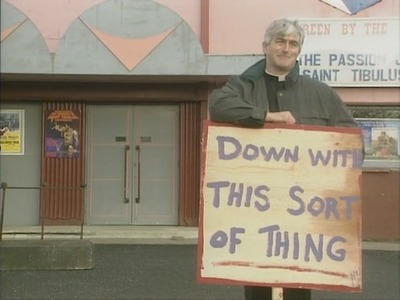 "Shows Father Ted holding a sign saying ""Down with this sort of thing"" outside a cinema"